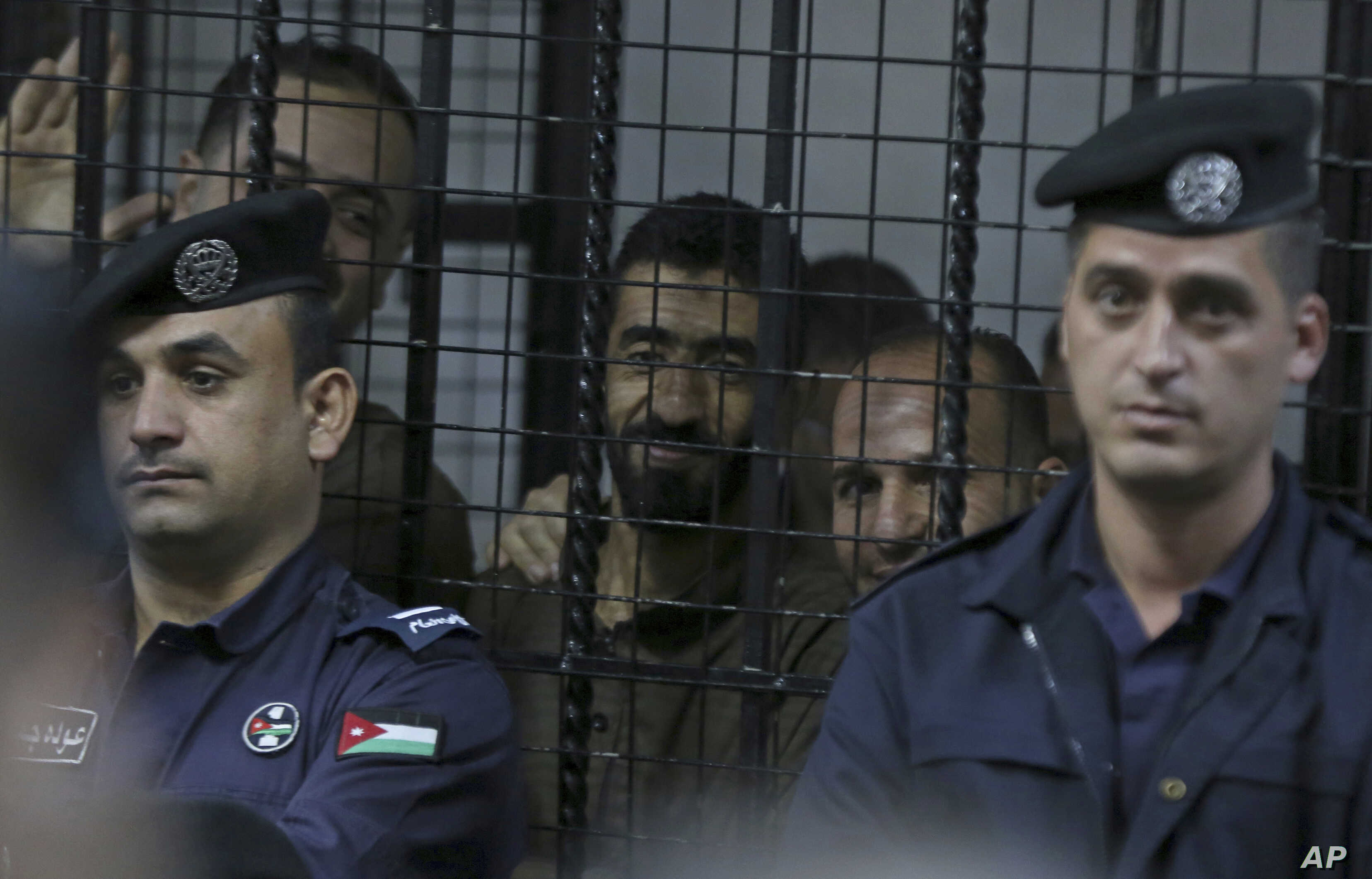 Guards surround the defendants' cage in state security court as judges sentenced 10 defendants to prison, with terms ranging from three years to life, for their role in an Islamic State attack on the Karak castle, a popular tourist site, Nov. 13, 201