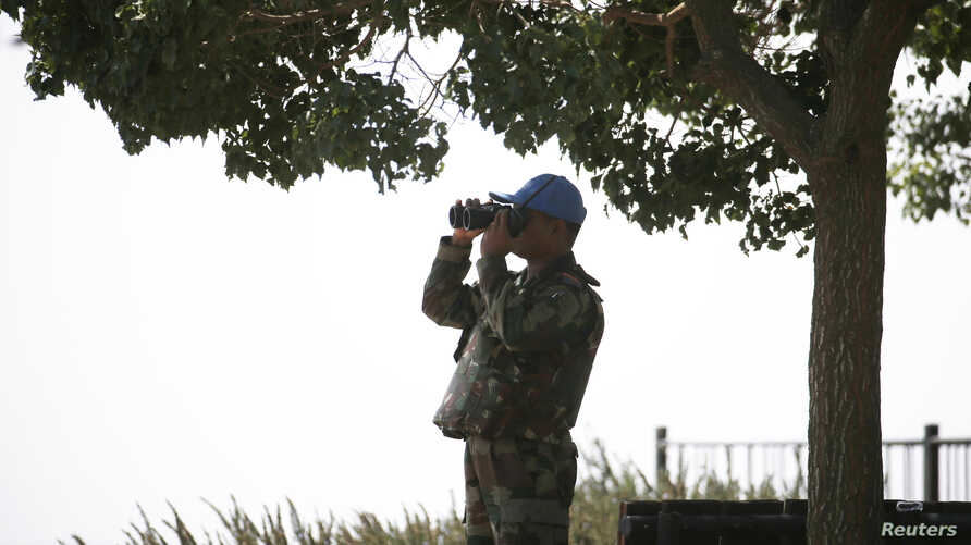 A member of the U.N. Disengagement Observer Force (UNDOF) looks through binoculars at the Syrian side of the Qunietra crossing from the Israeli-occupied Golan Heights, Sept. 1, 2014.