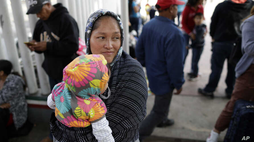 Maria Rafaela Blancante, of the Mexican state of Michoacan, holds her daughter, Jazmin, as they wait with other families to request political asylum in the United States, across the border in Tijuana, Mexico.