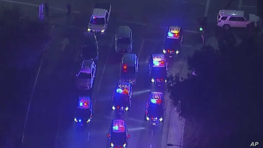 In this image made from aerial video, police vehicles block an intersection in the vicinity of a shooting in Thousand Oaks, California, early Nov. 8, 2018. Authorities say there were multiple injuries, including one officer.