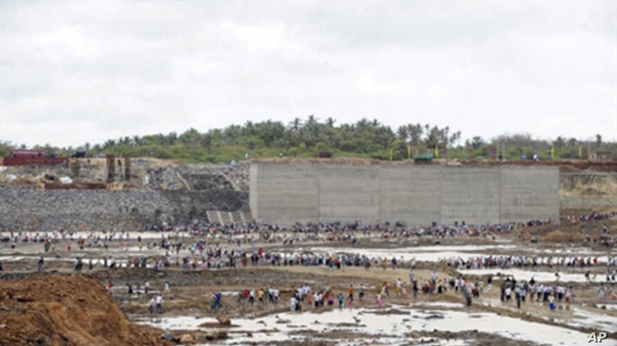 Guest and workers look on as the basin of  the under-construction port at Hambantota is being filled with sea water, 15 Aug 2010