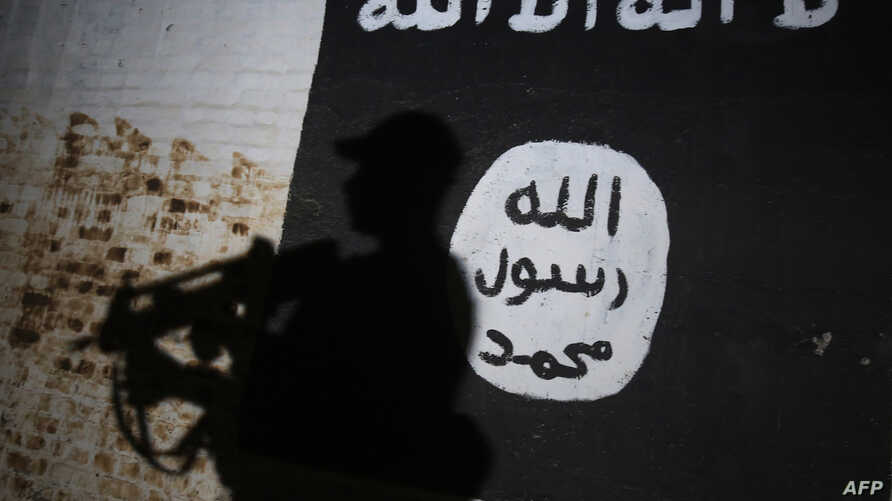 A member of the Iraqi forces walks past a mural bearing the logo of the Islamic State group in a tunnel that was reportedly used as a training center by the jihadists, on March 1, 2017, in the village of Albu Sayf, on the southern outskirts of Mosul.