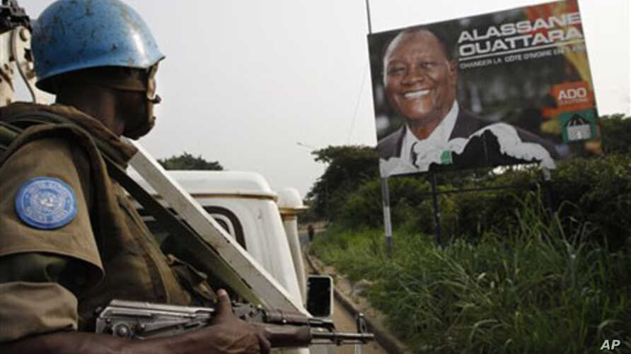 United Nations troops from Niger drive past a billboard of Ivory Coast's internationally recognized elected leader Alassane Ouattara during a patrol in Abidjan, Ivory Coast, Tuesday, Jan. 4, 2011.