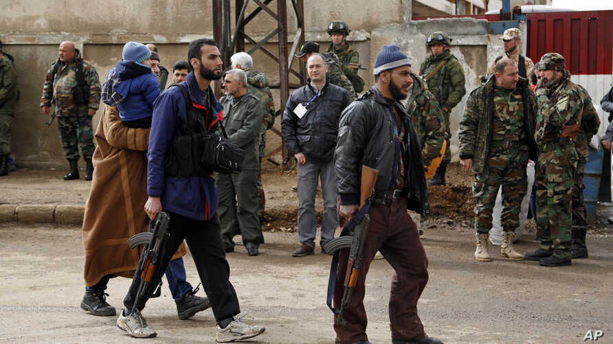 Gunmen carrying their weapons and some family members leave the al-Waer neighborhood bound for a town on the Turkish border, in Homs, Syria, Saturday, March 18, 2017.