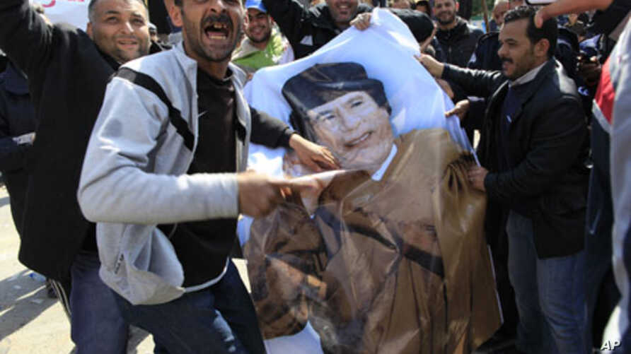 Protesters deface a poster of Libyan leader Moammar Gadhafi in the city of Zawiyah, February 27, 2011
