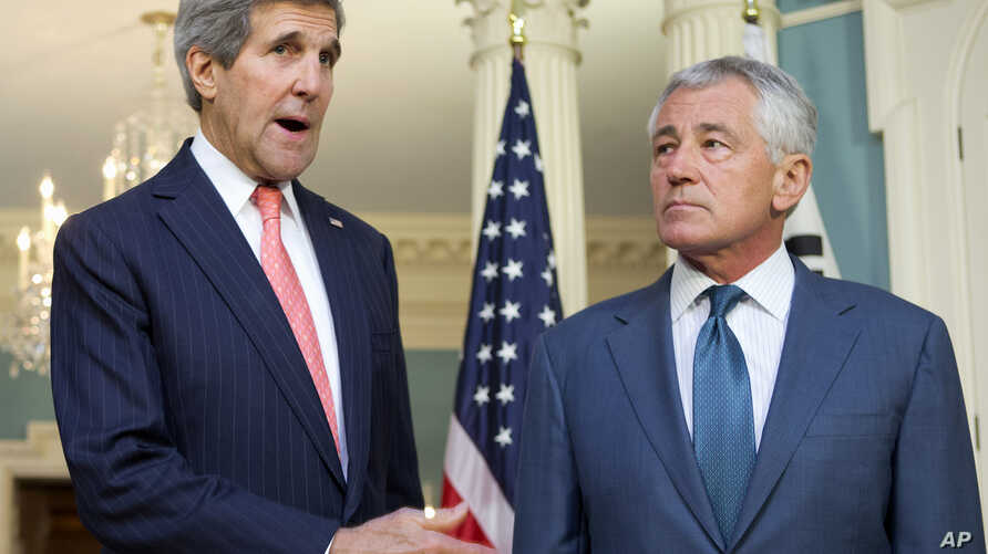 Secretary of State John Kerry, left, joined by Defense Secretary Chuck Hagel, speaks to media at the State Department in Washington, Friday, Oct. 24, 2014.