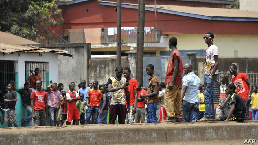FILE - Demonstrators gather during clashes between security forces and demonstrators at an unauthorized anti-government protest in Conakry, April 20, 2015.