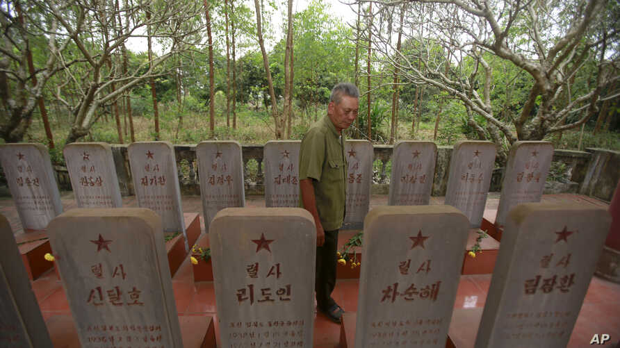 War veteran Duong Van Dau walks in between a row of headstones at a memorial for North Korean fallen pilots in Bac Giang province, Vietnam, Feb. 16, 2019.