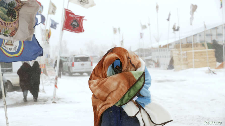 "A camper braces against high winds and a blizzard while walking inside the Oceti Sakowin camp as ""water protectors"" continue to demonstrate against plans to pass the Dakota Access pipeline adjacent to the Standing Rock Sioux Reservation, near Cannon"