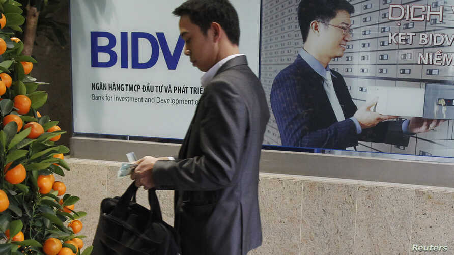 FILE - A man counts money he withdrew from an ATM machine at the headquarters of the Bank for Investment and Development of Vietnam in Hanoi.