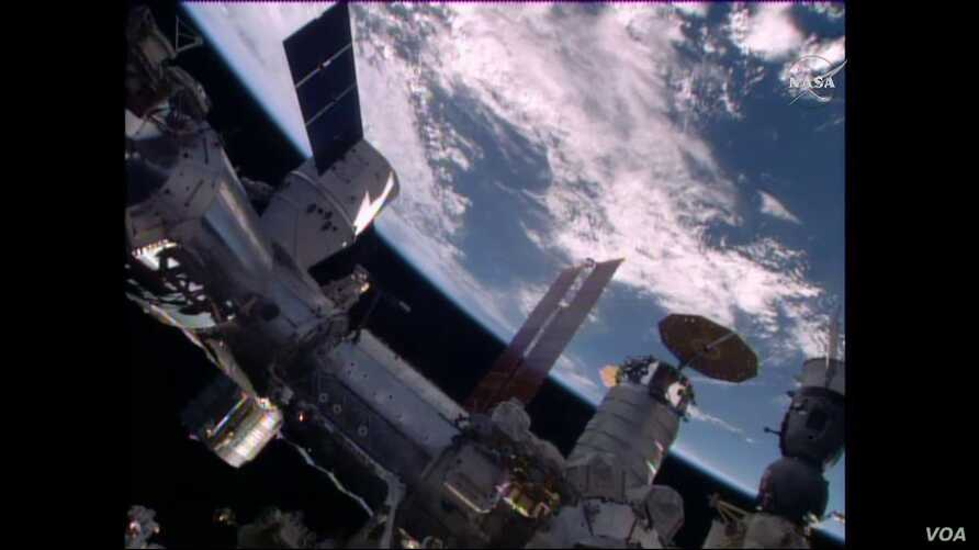 The SpaceX Dragon is seen shortly after it was mated to the Harmony module, April 10, 2016. The Cygnus cargo craft with its circular solar arrays and the Soyuz TMA-19M spacecraft (bottom right) are also seen in this view. (Credit: NASA TV)