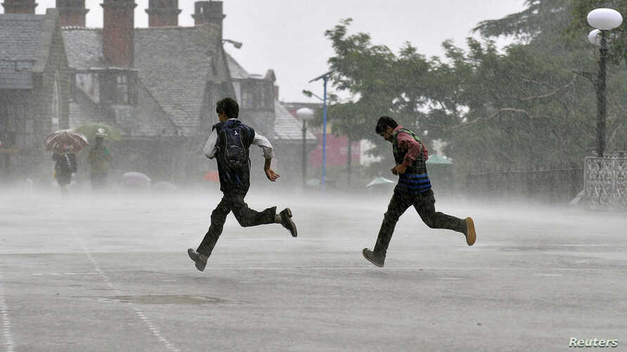 Men run for cover during a heavy rain shower in the northern Indian hill town of Shimla, July 4, 2014.
