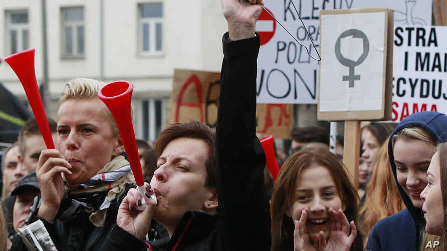 Polish women and some male supporters blow horns while raising a hanger, the symbol of illegal abortion, during a nationwide strike and demonstration to protest a legislative proposal for a total ban on abortion in Warsaw, Oct. 3, 2016.