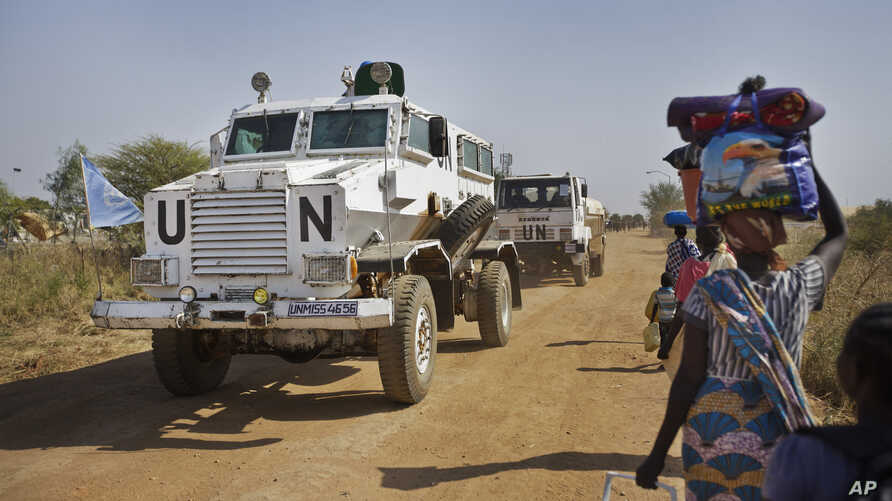 FILE - Displaced people are passed by a United Nations vehicle while walking towards a U.N. camp in Malakal, South Sudan, December 30, 2013. The U.N. is now helping thousands of families in the state of Yei River displaced by months of fighting.
