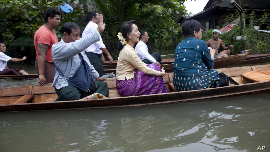 Myanmar opposition leader Aung San Suu Kyi, center, rides a boat on her way to a monastery where flood victims are sheltered, Aug. 3, 2015, in Bago, 80 kilometers (50 miles) northeast of Yangon, Myanmar.