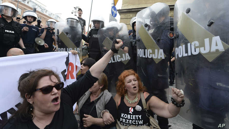 FILE - In this May 1, 2018, file photo, anti-fascists shout slogans against members of the far-right National-Radical Camp in Warsaw, Poland.