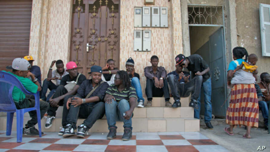 Rappers and musicians in Senegal's Y'en a Marre (We're Fed Up) coalition sit in Dakar while waiting to make a music video.