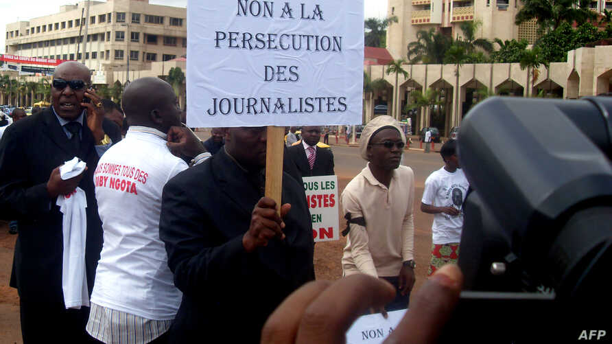 "FILE - A Cameroonian journalist holds a sign raeding ""No to the persecution of journalists"" during a free speech rally in Yaounde, Cameroon, May 3, 2010."