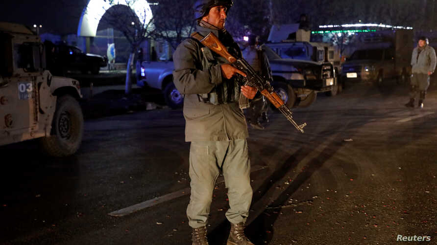 An Afghan police officer keeps watch at the site of a suicide bomb attack in Kabul, Afghanistan Nov. 20, 2018.  It is suspected the bombing could be the work of Islamic State's Afghan branch, known as IS Khorasan Province or ISK-P.