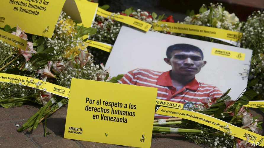 "FILE - Photo of a Venezuela citizen is seen in front of Venezuela's embassy building during a protest by the human rights organization Amnesty International in Lima, Peru, April 12, 2018. The signs on the ground read in Spanish ""Respcet human rights"