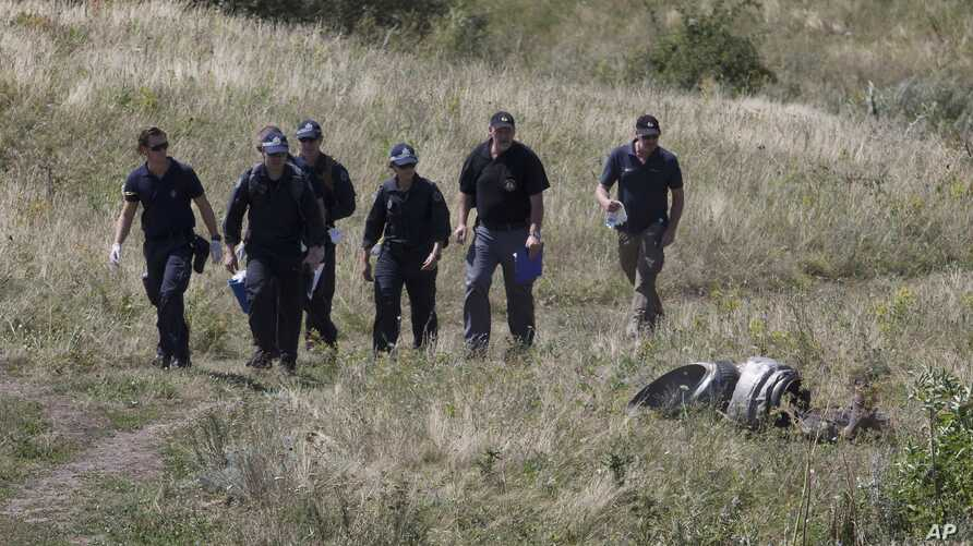 Australian experts examine the area of the Malaysia Airlines Flight 17 plane crash in the village of Hrabove, Donetsk region, eastern Ukraine, Aug. 1, 2014.