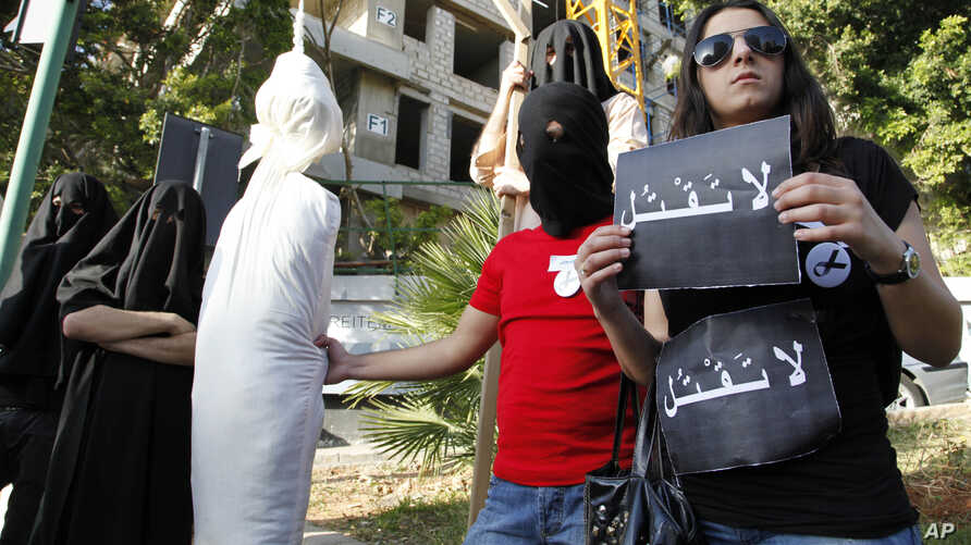 FILE - In this Thursday, April 1, 2010 file photo, activists from a civil organization reenact an execution scene in front of the Saudi Arabia Embassy in Beirut, Lebanon, as they protest a possible beheading of a Lebanese man accused of witchcraft in...