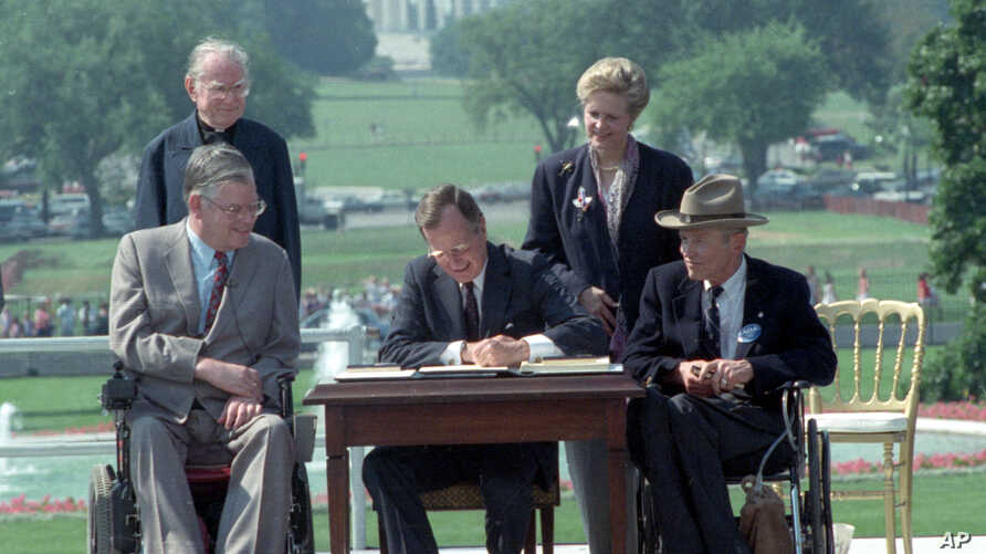 President George Bush signs the Americans with Disabilities Act during a ceremony on the South Lawn of the White House July 26, 1990.