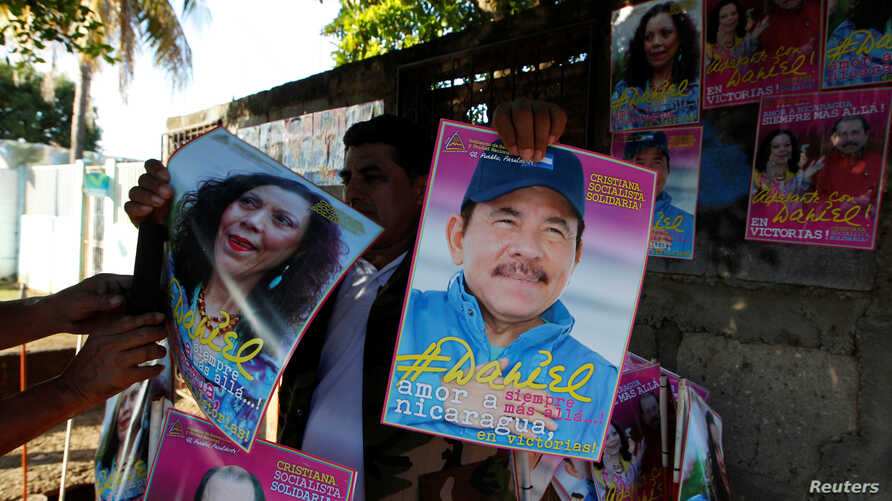 A man holds campaign posters in support of Nicaragua's President Daniel Ortega and vice presidential candidate first lady Rosario Murillo in Managua, Oct. 27, 2016.