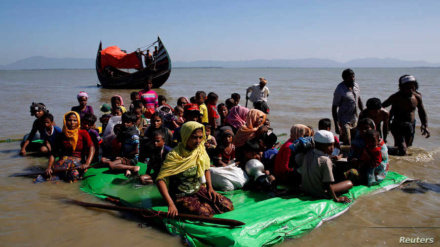 Rohingya refugees sit on a makeshift boat as they await permission from Border Guard Bangladesh to continue after crossing the Bangladesh-Myanmar border, at Shah Porir Dwip near Cox's Bazar, Bangladesh, Nov. 9, 2017.
