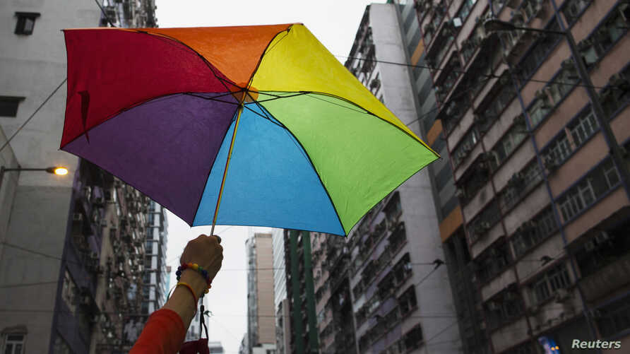 A participant holds a rainbow umbrella as he attends a lesbian, gay, bisexual and transgender (LGBT) Pride Parade in Hong Kong, Nov. 8, 2014.