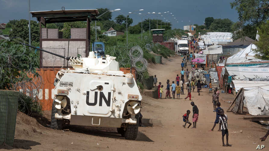 Some of the more than 30,000 Nuer civilians sheltering in a U.N. base in South Sudan's capital, Juba, for fear of targeted killings by government forces walk by an armored vehicle and a watchtower manned by Chinese peacekeepers, July 25, 2016.