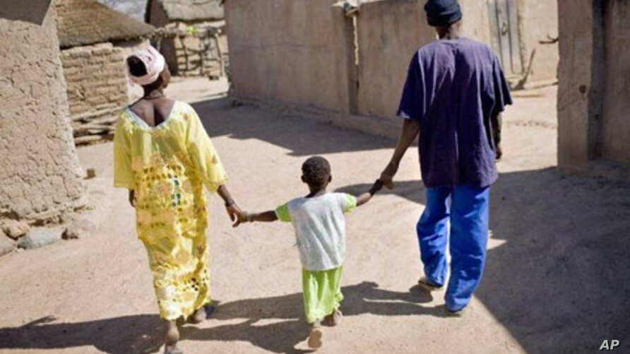 Health worker (right) walks with a mother and her child in Satiguila, Mali.