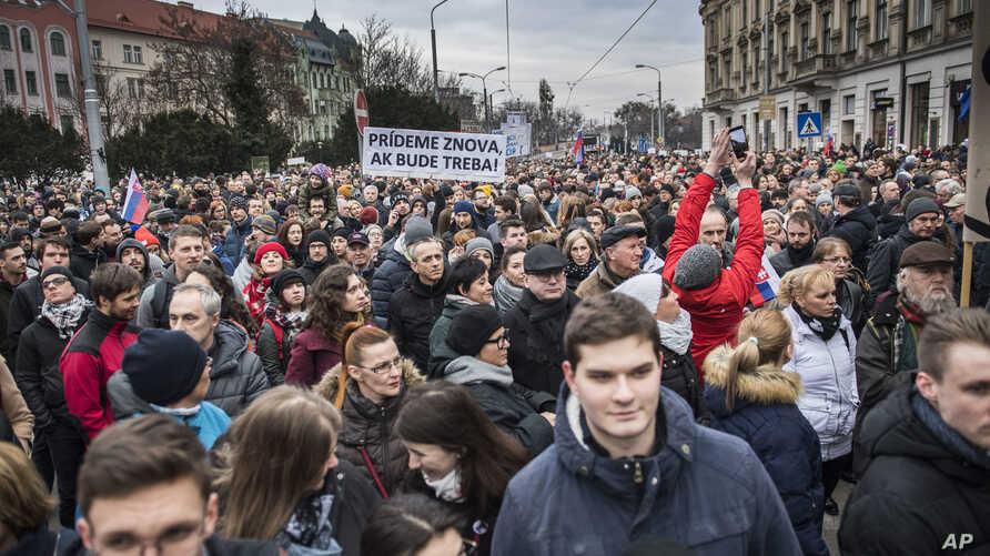 """Protesters hold a banner reading """"I do care about it"""" during a mass quiet march in Bratislava, Slovakia, March 23, 2018.  Many thousands of Slovaks took to the streets in anti-government protests amid a continuing political crisis triggered by the re"""