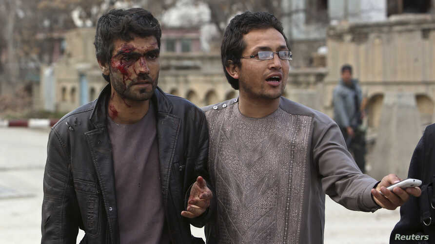 An Afghan man helps an injured man at the site of an attack in Kabul, March 28, 2014.