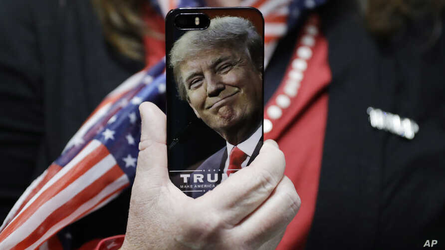 FILE - A woman holds up her cell phone before a rally with Republican presidential candidate Donald Trump in Bedford, New Hampshire, Sept. 29, 2016. In an interview to air later Sunday, Trump has signalled that as president he will exercise more rest