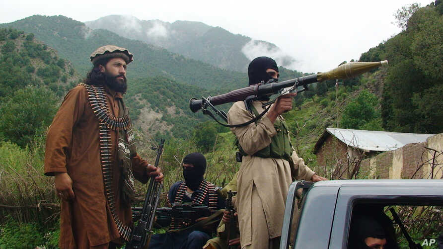 FILE - Pakistani Taliban patrol in their stronghold of Shawal in Pakistani tribal region of South Waziristan, Aug. 5, 2012.