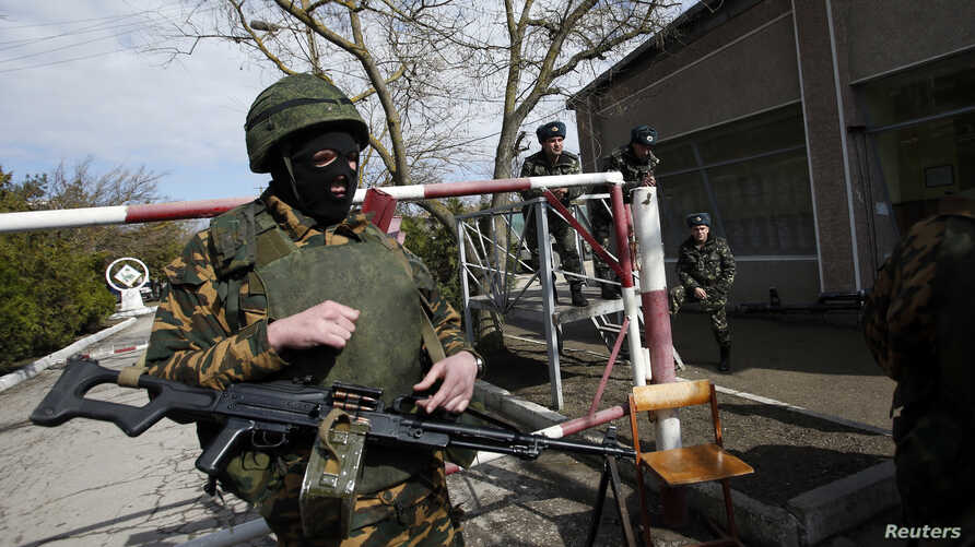 Ukrainian servicemen look on as an armed man, believed to be a Russian soldier, stands guard inside a Ukrainian military base in the Crimean town of Yevpatoria, March 5, 2014.