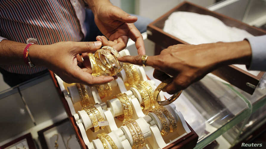 FILE - An employee shows gold bangles to a customer at a jewellery showroom on the occasion of Dhanteras, a Hindu festival associated with Lakshmi, the goddess of wealth, at a market in Mumbai, Nov. 1, 2013.