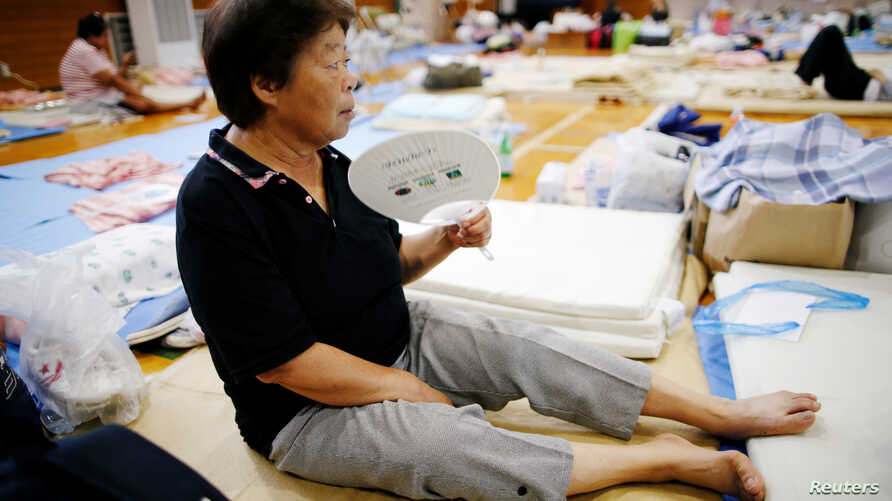 An evacuee uses a paper fan as she rests at Okada elementary school that is used as an evacuation center in Mabi town in Kurashiki, Okayama Prefecture, Japan, July 12, 2018.