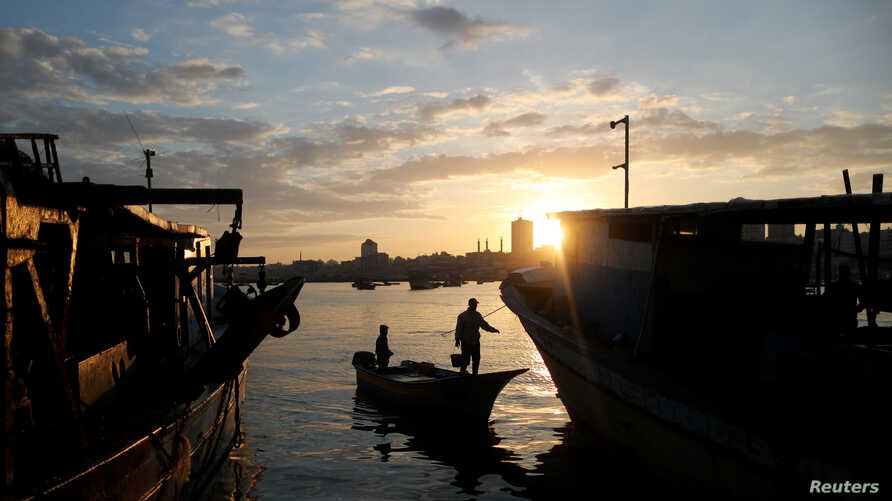 The sun rises as fishermen are seen at the seaport of Gaza City, after Israel expanded fishing zone for Palestinians, April 2, 2019.