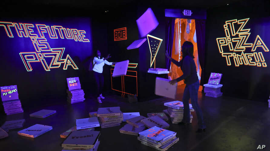 """A pizza box playroom created with neon lights and colorful fluorescent tape called """"Gazoo,"""" is part of a group art exhibition celebrating pizza at The Museum of Pizza in New York, Nov. 2, 2018."""