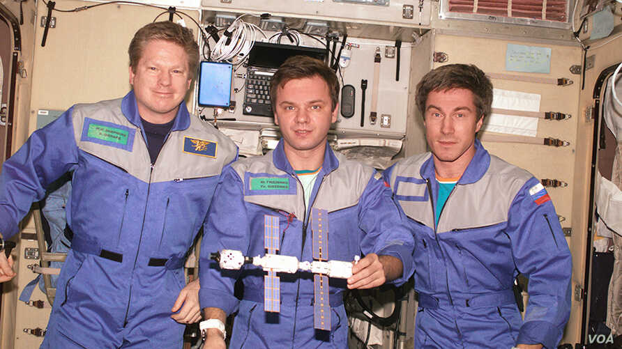 Expedition 1, the first space station crew, poses inside the Zvezda service module with a model of the young International Space Station. Pictured in December 2000 (from left) are Commander William Shepherd and Flight Engineers Yuri Gidzenko and Serg
