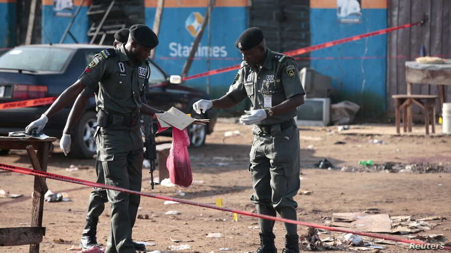 Police bomb squad personnel gather debris for analysis at the scene of a bomb blast in Nyanya, on the outskirts of Abuja, Nigeria, Oct. 3, 2015.
