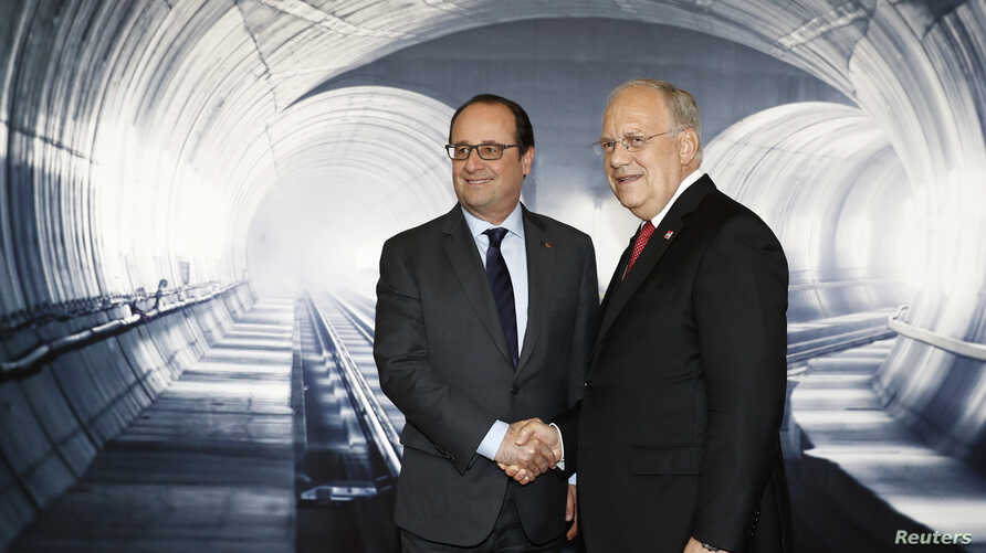 Swiss Federal President Johann Schneider-Ammann, right, speaks with French President Francois Hollande, left, on the opening day of the Gotthard rail tunnel, the longest tunnel in the world, at the fairground Rynaecht at the northern portal in Erstfe