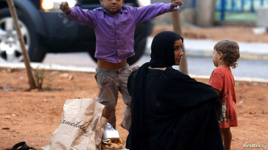 A homeless Syrian woman and her children are seen along a street in Beirut, July 22, 2013.