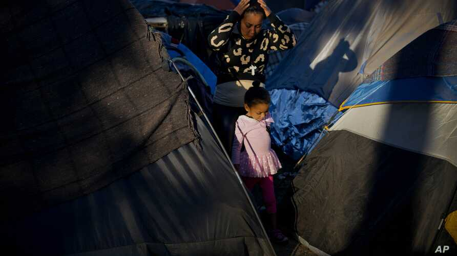 A woman and a girl who traveled a caravan of migrants walks between tents at the Benito Juarez Sports Center which is serving as a shelter in Tijuana, Mexico, Nov. 26, 2018.