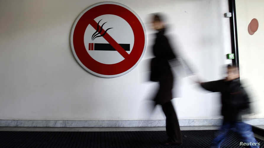 "A woman walks past a ""No Smoking"" sign in Nice"