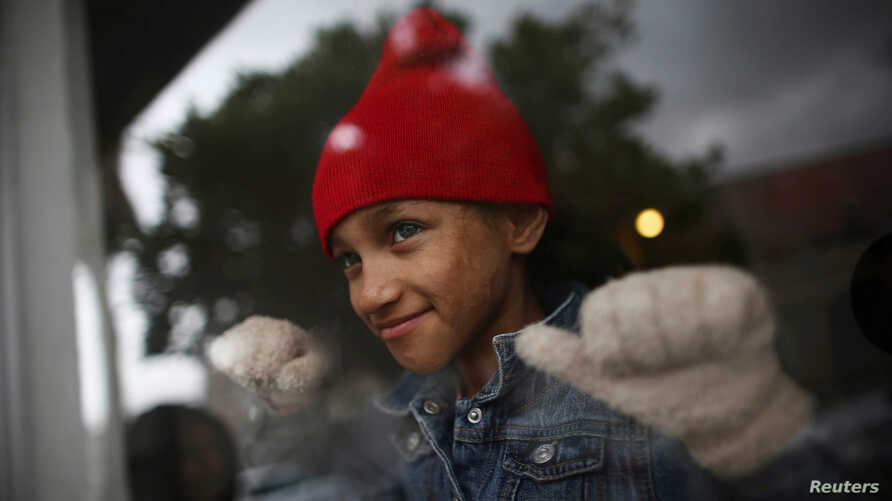 Ashley, 8, from Honduras and a member of a caravan of migrants from Central America, looks through the window of a restaurant near the San Ysidro checkpoint as the first fellow migrants entered U.S. territory to seek asylum on Monday, in Tijuana, Mex