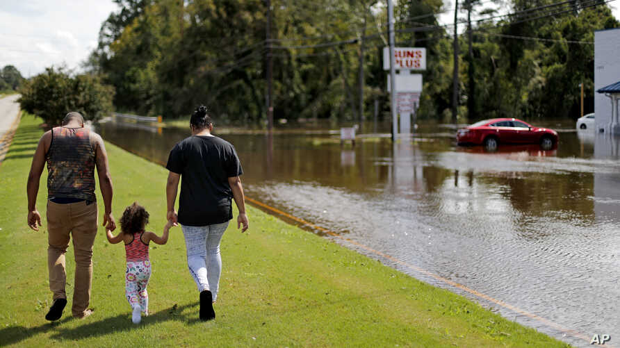 A couple walks with their daughter after checking on their flooded home in the aftermath of Hurricane Florence in Spring Lake, N.C., Monday, Sept. 17, 2018.