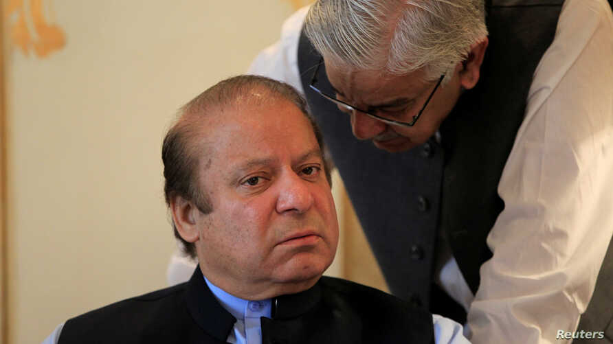 Former Pakistani Prime Minister Nawaz Sharif speaks with an official during a meeting in Islamabad, Aug. 9, 2017.